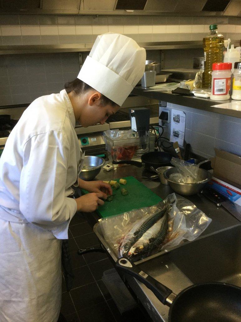 Etudiante d'école hôtelière cuisinant du poisson
